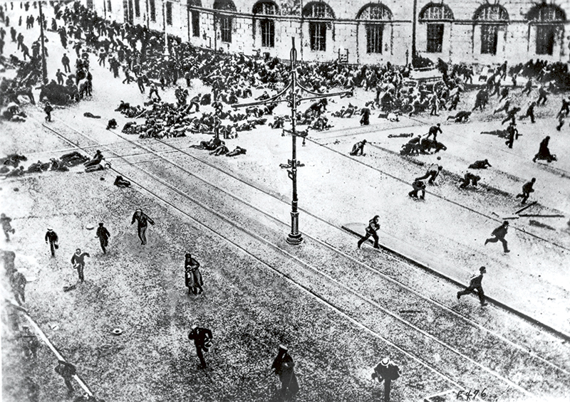 FILE - In this May 1917 file photo, a scene on the main street in St. Petersburg, Russia, (during communist times called Petrograd), during the revolution when the revolutionists turned on their machine guns. The tumult that Russia endured in 1917 sent shockwaves around the world as its last czar, Nicholas II, abdicated his throne, and power was later seized by Vladimir Lenin's Bolsheviks. A century later, the anniversary is being marked with little official commemoration from the Kremlin. (AP Photo, File)