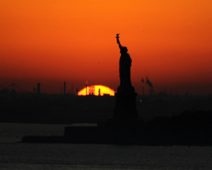 The sun sets behind the Statue of Liberty in New York, Sunday, Nov. 8, 2009. (AP Photo/Benny Snyder)