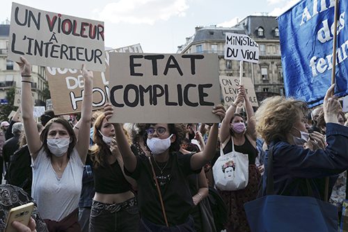 Women's rights activists protest against French President Emmanuel Macron's appointment of an interior minister who has been accused of rape and a justice minister who has criticized the #MeToo movement, in front of Paris city hall, in Paris, France, Friday, July 10, 2020. The French government said it remains committed to gender equality and defended the new ministers, stressing the presumption of innocence. Gerald Darmanin, Interior Minister, firmly denies the rape accusation, and an investigation is underway. New Justice Minister Eric Dupond-Moretti is a lawyer who has defended a government member accused of rape and sexual assault, and has ridiculed women speaking out thanks to the #MeToo movement. (AP Photo/Francois Mori) XFM126